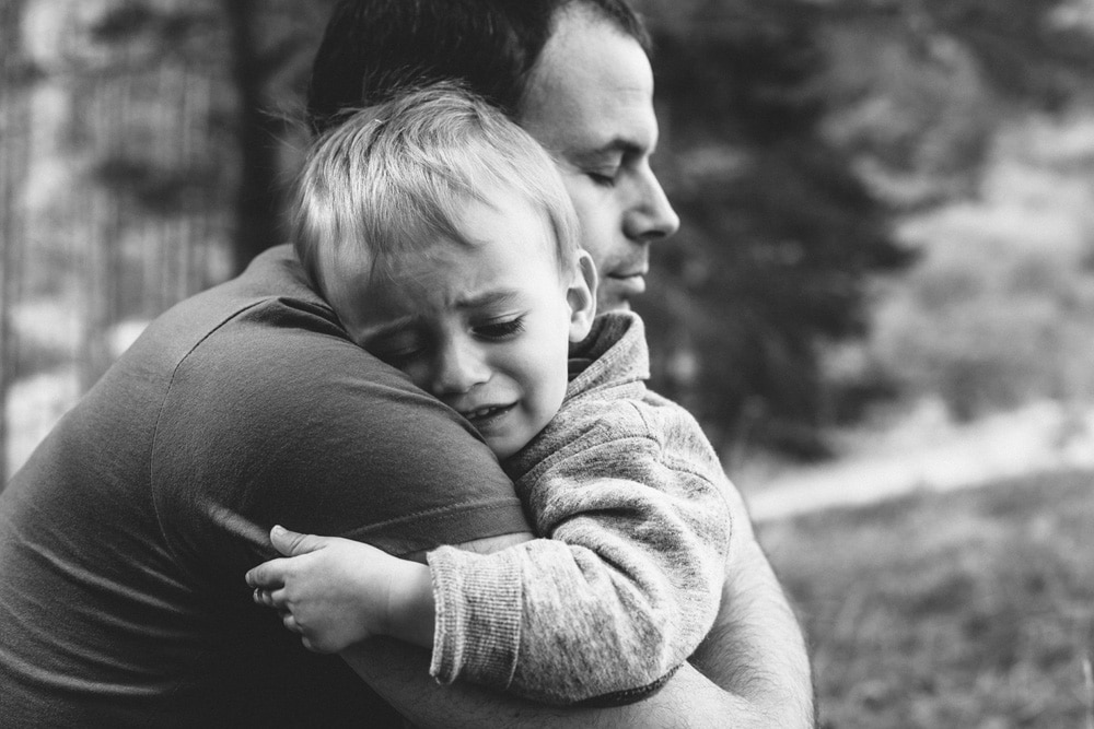Child Custody - Father hugging his crying son - Little boy crying on father's shoulder